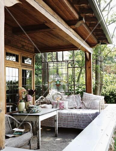 gem tliche verandaecke eines landhauses mit tagesbett und kissen vor bleiglaswand und blick auf. Black Bedroom Furniture Sets. Home Design Ideas