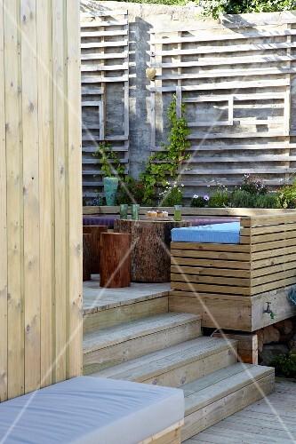 sitzbank aus holzst ben auf terrasse mit zwei ebenen und pflanzenger st an natursteinmauer. Black Bedroom Furniture Sets. Home Design Ideas