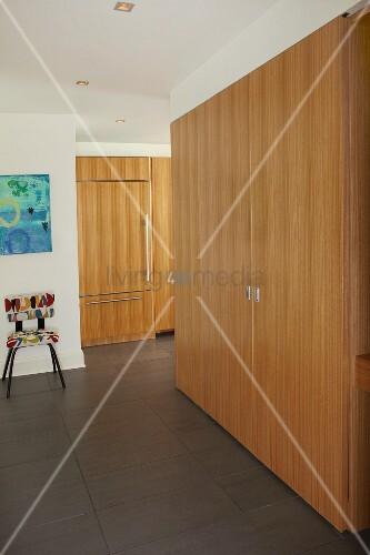 Einbauschrank aus Holz in modernem Flur und Blick in offene Küche ...