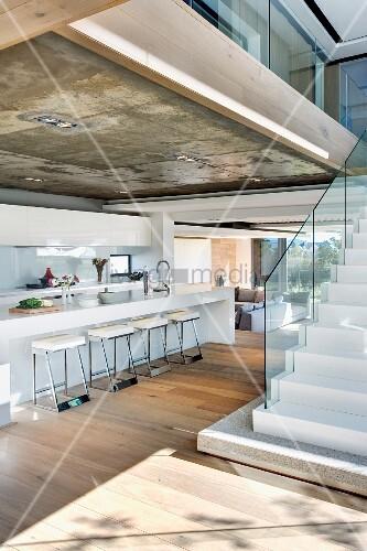 thekenk che unter sichtbetondecke und freistehende treppe mit glasbr stung im offenen wohnraum. Black Bedroom Furniture Sets. Home Design Ideas