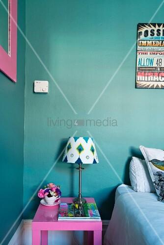 pinkfarbener nachtisch und lampe mit gemustertem schirm vor t rkis wand bild kaufen living4media. Black Bedroom Furniture Sets. Home Design Ideas