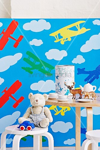 kinderstuhl und tisch mit spielsachen kindergeschirr und spardose vor tapete mit flugzeugmotiv. Black Bedroom Furniture Sets. Home Design Ideas