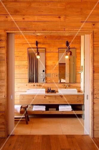 Badezimmer aus holz mit zwei waschbecken und langem holzwaschtisch