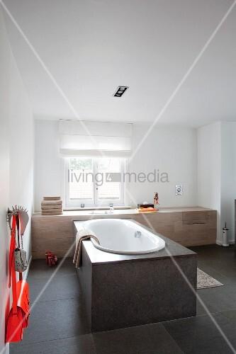 freistehende badewanne mit steinverkleidung vor fenster in minimalistischem bad bild kaufen. Black Bedroom Furniture Sets. Home Design Ideas