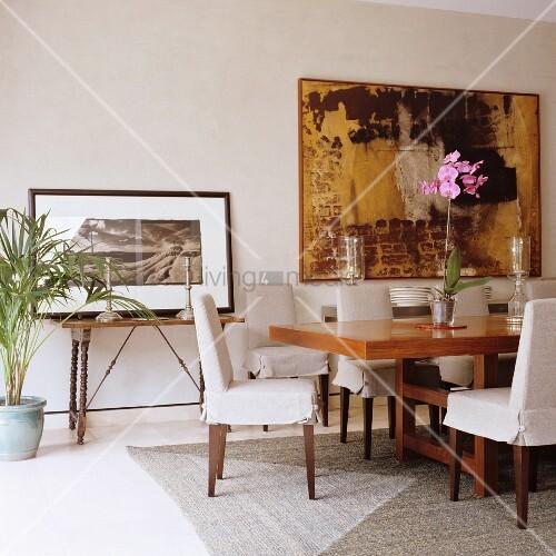 hussenst hle an langem edelholztisch und moderne kunst an der wand in klassischem elegantem. Black Bedroom Furniture Sets. Home Design Ideas