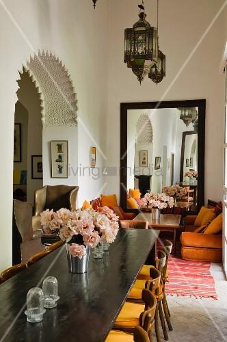 marokkanische laternenleuchten ber langem esstisch und sitzecke mit wandspiegel im hintergrund. Black Bedroom Furniture Sets. Home Design Ideas