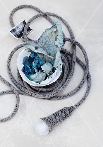 getrocknete und eingef rbte bl ten in einer schale aufgrolltes kabel mit gl hbirne und strick. Black Bedroom Furniture Sets. Home Design Ideas