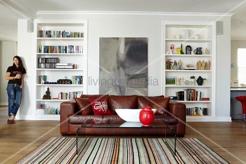 plexiglas couchtisch auf gestreiftem teppich und ledercouch vor einbauregal frau im hintergrund. Black Bedroom Furniture Sets. Home Design Ideas