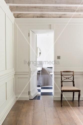 eine in der wei en holzvert felung versteckte t r fffnet sich zum g stebad in einem. Black Bedroom Furniture Sets. Home Design Ideas