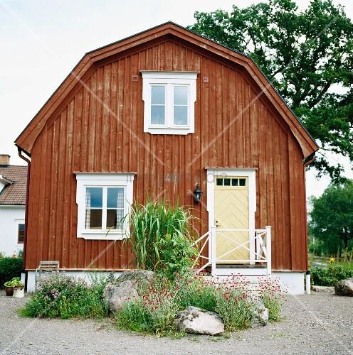 traditionelles skandinavisches holzhaus mit mansarddach und vorgartengestaltung mit findlingen. Black Bedroom Furniture Sets. Home Design Ideas