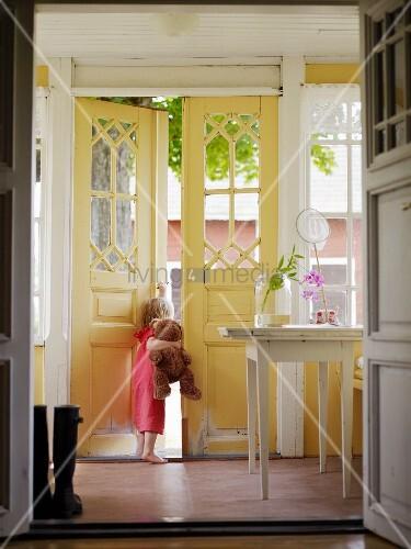 Geöffnete haustür  Mädchen mit Teddybär schaut aus geöffneter Haustür – Bild kaufen ...