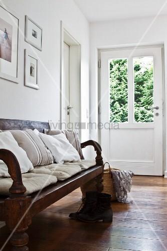 rustikale holzbank mit vielen kissen in der diele bild. Black Bedroom Furniture Sets. Home Design Ideas