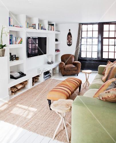 sofa mit kissen und gepolsterter couchtisch gegen ber wand mit gemauertem regal und aufgeh ngtem. Black Bedroom Furniture Sets. Home Design Ideas