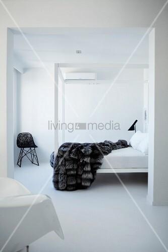 weisses minimalistisches schlafzimmer mit fell tagesdecke auf himmelbett in zimmerecke ein. Black Bedroom Furniture Sets. Home Design Ideas