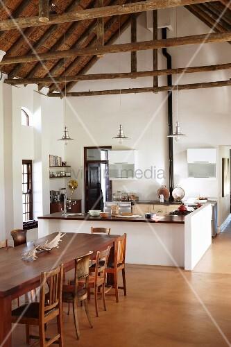 Esstisch mit verschiedenen Holzstühlen vor offener Küche mit Theke ...