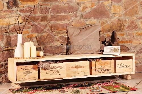 selbst gebautes sideboard mit weinkiste als stauraum vor natursteinwand bild kaufen living4media. Black Bedroom Furniture Sets. Home Design Ideas