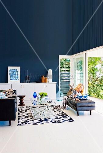 Elegantes Wohnzimmer mit dunkelblauer Wand, lesende Frau vor offener ...