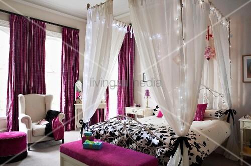 elegantes schlafzimmer mit beleuchtetem himmelbett und textilien in lila bild kaufen. Black Bedroom Furniture Sets. Home Design Ideas
