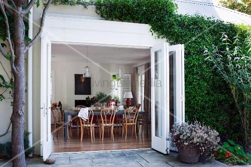 blick von terrasse durch offene faltt r auf thonet st hle. Black Bedroom Furniture Sets. Home Design Ideas