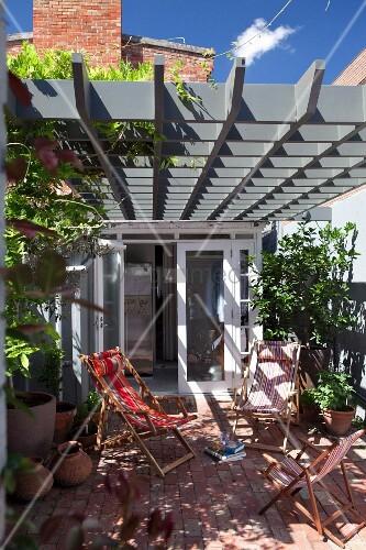 sonnenbeschienene liegest hle auf terrasse unter pergola. Black Bedroom Furniture Sets. Home Design Ideas