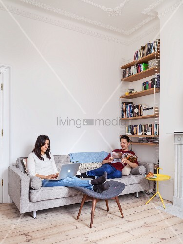 junges paar entspannt mit zeitschrift und laptop auf grauem sofa sitzend in renovierter. Black Bedroom Furniture Sets. Home Design Ideas