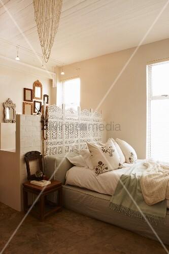 romantisches schlafzimmer mit pastellgr nem polsterbett und kunstvollem wei em paravent vor. Black Bedroom Furniture Sets. Home Design Ideas