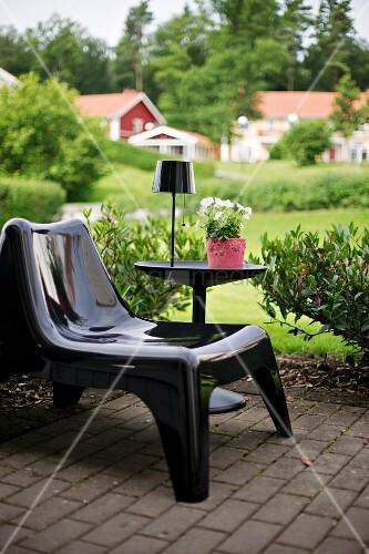 schwarzer kunststoff sessel neben beistelltisch mit. Black Bedroom Furniture Sets. Home Design Ideas