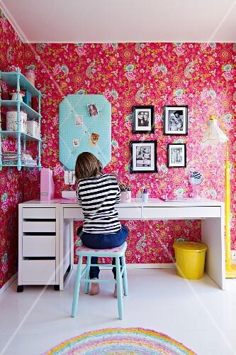 junges m dchen am schreibtisch in nostalgischem kinderzimmer an wand tapete mit blumenmuster. Black Bedroom Furniture Sets. Home Design Ideas