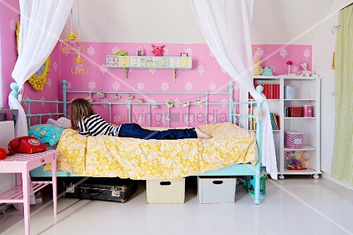 junges m dchen auf himmelbett mit weissem drapiertem vorhang an wand rosa tapete mit. Black Bedroom Furniture Sets. Home Design Ideas