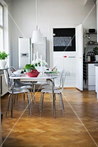 Gedeckter Tisch Und Weisse Schalenstühle Im Retro Stil In Modern  Eingerichtetem Esszimmer Mit Fischgrät Parkett