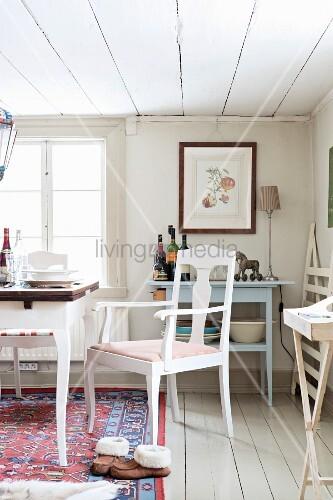 weiss lackierter stuhl neben teilweise sichtbarem tisch vor fenster in l ndlichem esszimmer. Black Bedroom Furniture Sets. Home Design Ideas