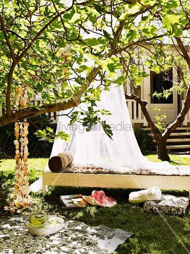 schattiges pl tzchen im garten luftiger baldachin ber tagesbett aus rattan davor. Black Bedroom Furniture Sets. Home Design Ideas