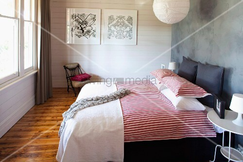 doppelbett mit rot weiss gestreifter bettw sche an grauer wand im hintergrund weisse holzwand. Black Bedroom Furniture Sets. Home Design Ideas