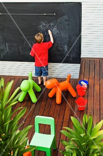 terrasse mit kinder spielsachen auf holzboden kleiner junge vor schiefertafel beim zeichnen. Black Bedroom Furniture Sets. Home Design Ideas