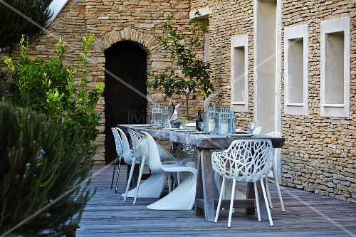 weisse outdoor st hle um rustikalem holztisch auf terrasse vor mediterranem natursteinhaus. Black Bedroom Furniture Sets. Home Design Ideas