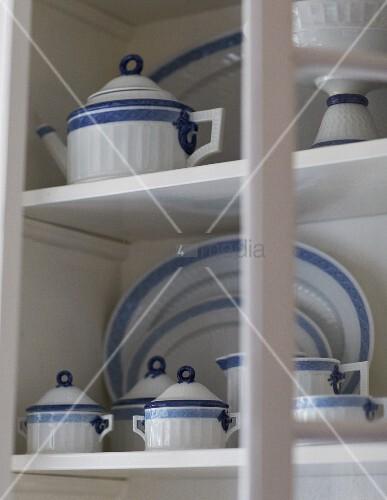 weiss blaues geschirr auf weissen ablagen im schrank. Black Bedroom Furniture Sets. Home Design Ideas