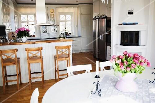 tulpenstrausss auf weissem esstisch im hintergrund theke und barhocker vor offener. Black Bedroom Furniture Sets. Home Design Ideas