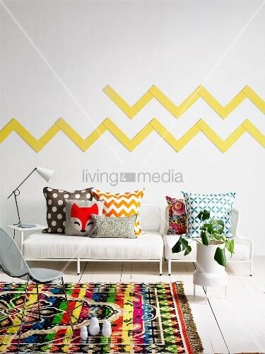 bunter gemusterter teppich auf weissem dielenboden vor polsterbank mit kissen in verschiedenen. Black Bedroom Furniture Sets. Home Design Ideas