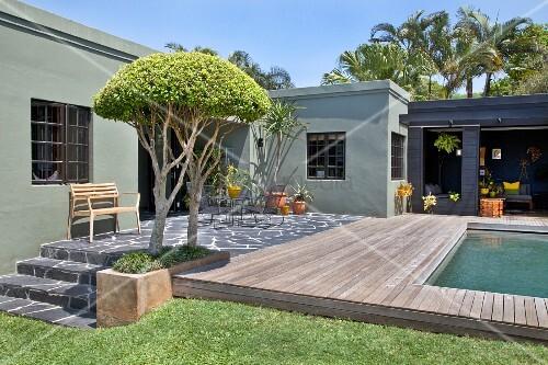 sommerstimmung im garten terrasse mit natursteinbelag und pool vor bungalow im hintergrund. Black Bedroom Furniture Sets. Home Design Ideas