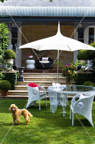 weisse rattanst hle und glastisch unter pagode sonnenschirm vor terrasse mit stufen im. Black Bedroom Furniture Sets. Home Design Ideas
