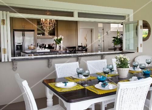 weisse rattanst hle um gedeckten tisch in der loggia vor. Black Bedroom Furniture Sets. Home Design Ideas