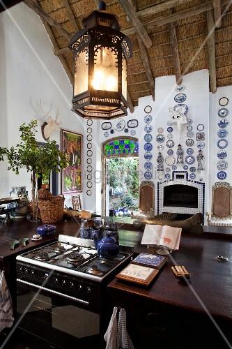 aufgeh ngte laterne ber k chentheke aus dunklem holz mit gaskochfeld bild kaufen living4media. Black Bedroom Furniture Sets. Home Design Ideas