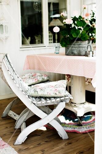 weiss lackierte holzst hle vor tisch mit blumentopf in. Black Bedroom Furniture Sets. Home Design Ideas