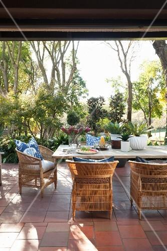 Rattanst hle und holztisch auf terracotta terrasse und garten im hintergrund bild kaufen - Holztisch terrasse ...