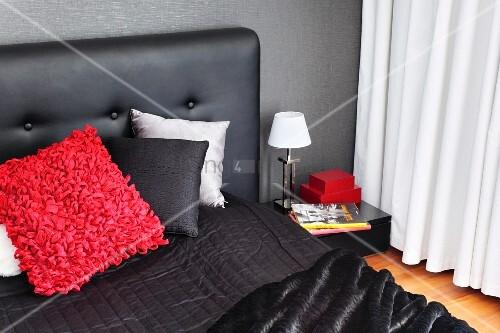 kissen auf schwarzem bett mit gepolstertem kopfteil vor dunkler wand. Black Bedroom Furniture Sets. Home Design Ideas