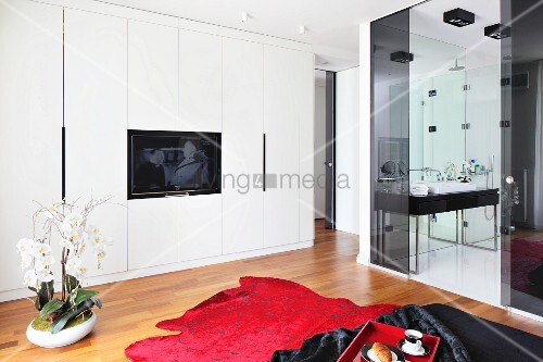 orchideen im topf neben rotem teppich auf parkettboden an der wand weisser einbauschrank mit. Black Bedroom Furniture Sets. Home Design Ideas