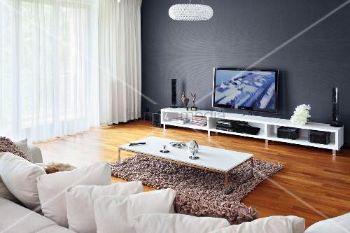 Kissenreihe auf sofa und couchtisch auf flokatiartigem for Grauer couchtisch