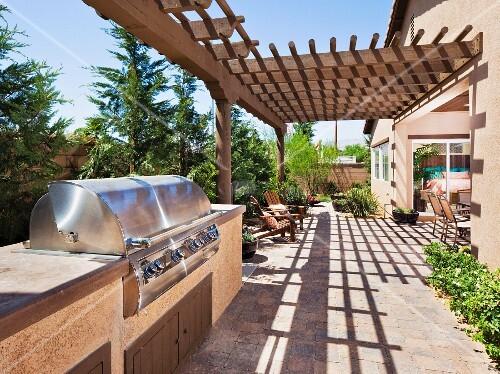 aussengrill aus edelstahl auf terrasse teilweise mit pergola aus holz vor sonnenbeschienenem. Black Bedroom Furniture Sets. Home Design Ideas