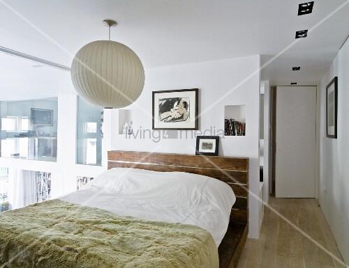 tagesdecke auf doppelbett unter weisser kugellampe im schlafzimmer bild kaufen living4media. Black Bedroom Furniture Sets. Home Design Ideas