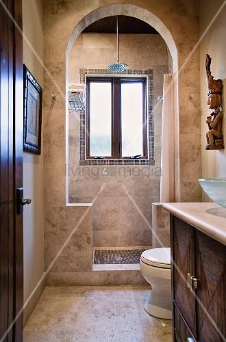 Gefliestes Badezimmer in Brauntönen mit Waschtisch & bogenförmigen Durchgang zur Dusche – Bild ...